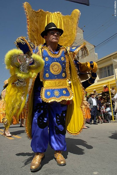 La Morenada dancer dressed in a blue-yellow extravagant costume.