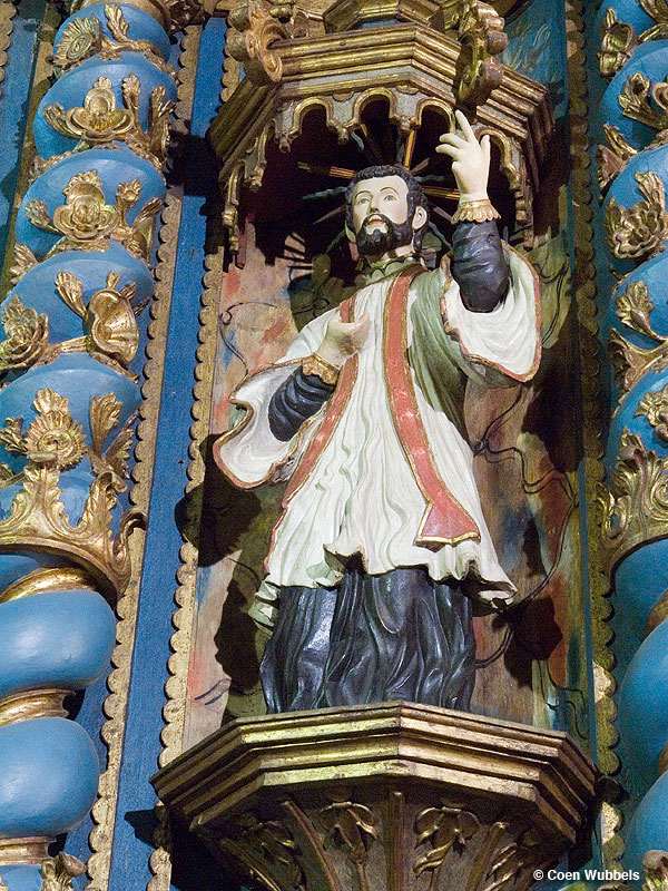 Franciscan Churches in Paraguay, here: a carved image of a Franciscan in white habit in a niche against blue-gold altar
