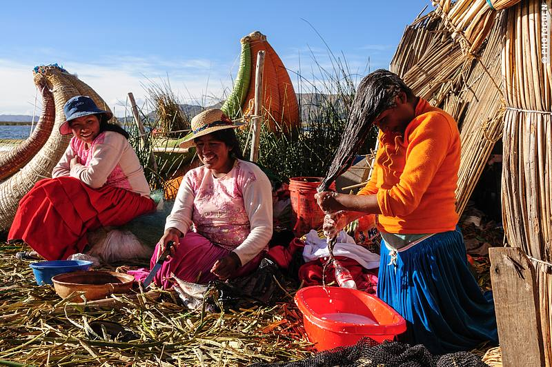 Uros People in Peru; here three women sitting on the reed island, one washing her hair, and behind them two torora reed boats